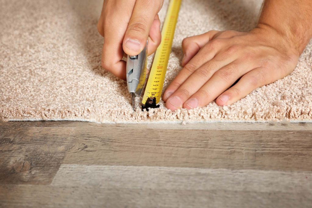 Man cutting new carpet flooring indoors, closeup. Space for text