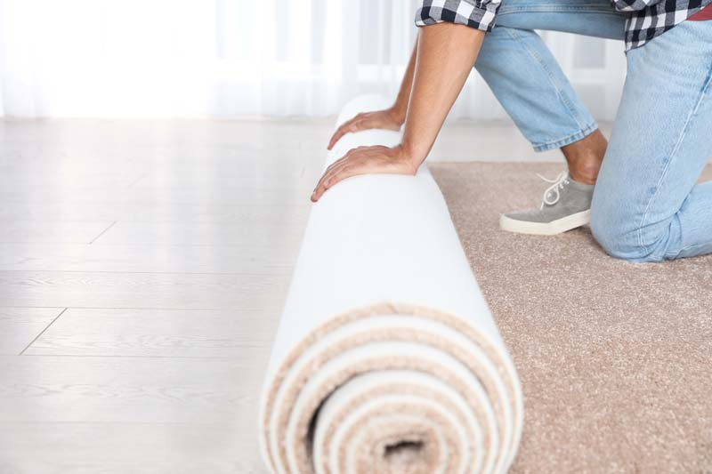 Man rolling out new carpet flooring indoors, closeup. Space for